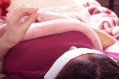 Femme vérifiant sa température corporelle Image libre de droits