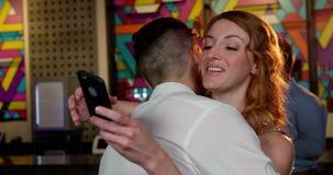 Femme vérifiant son téléphone portable tout en embrassant un homme banque de vidéos