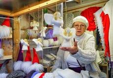 Femme vendant les statues faites main d'ange au marché de Noël de Riga Photos stock