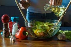Femme versant l'huile d'olive dans la salade saine sur la cuisine image libre de droits