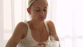 Femme versant la tisane chaude dans la tasse en verre transparente dans le mouvement lent Petit déjeuner sain à la maison banque de vidéos