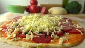 Femme versant le fromage râpé au-dessus de la pizza faite maison Cuisson, une partie de l'ensemble fin 4K vers le haut de tir banque de vidéos