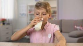 Femme versant le lait frais en verre pour le petit déjeuner sain du fils, nutrition de calcium banque de vidéos