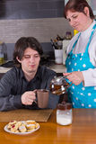 Femme versant le thé chaud dans la tasse du jeune homme Image libre de droits