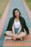 Femme verte de chemise s'asseyant sur la pelouse image stock