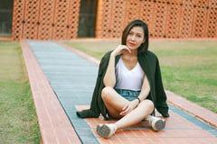 Femme verte de chemise s'asseyant sur la pelouse images stock