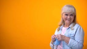 Femme vieillissante gaie tricotant et souriant ? la cam?ra, traditions de famille, passe-temps photos stock