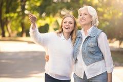 Femme vieillissante heureuse et fille mûre marchant en parc Images stock