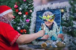 Femme vieillissante masquée appréciant le vin avec Santa Claus Image stock