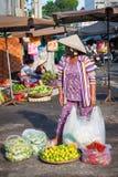 Femme vietnamienne dans le chapeau conique vendant des légumes au marché en plein air, Nha Trang Photographie stock libre de droits