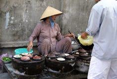 Femme vietnamienne sur le marché en plein air vendant des casse-croûte, passionnés sur un four spécial sur des charbons Photographie stock libre de droits