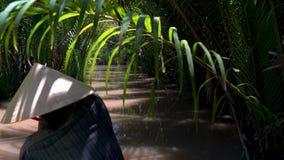 Femme vietnamienne utilisant un chapeau de feuille et barbotant un bateau ou un canoë traditionnel dans le delta du Mékong, Vietn clips vidéos