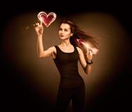 Femme visant au coeur rougeoyant avec une flèche Photo libre de droits