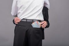 Femme volant l'argent dans la poche de son amant Photos libres de droits