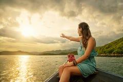 Femme voyageant en bateau appréciant le coucher du soleil parmi des îles photo stock