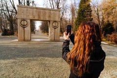 femme voyageant par la Roumanie Targu Jiu, embrassant la porte Photos stock