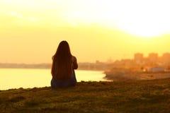 Femme voyant un coucher du soleil sur la ville image stock