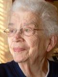 Femme White-haired regardant à l'extérieur l'hublot Photographie stock libre de droits