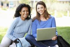 Femmes à l'aide de l'ordinateur portable dehors Image libre de droits