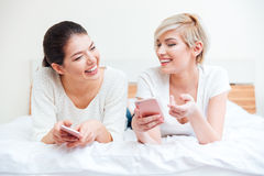 Femmes à l'aide des smartphones sur le lit Photos libres de droits