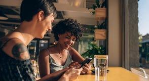 Femmes à l'aide des téléphones portables au café Photo stock