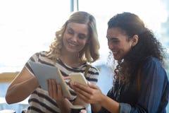 Femmes à l'aide du téléphone portable et du comprimé numérique dans le café Image stock