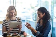 Femmes à l'aide du téléphone portable et du comprimé numérique tout en ayant la tasse de café Photographie stock libre de droits