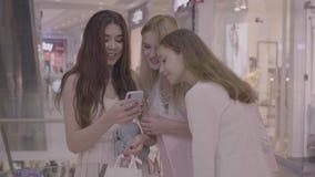 Femmes à la mode à l'aide du téléphone se tenant dans le centre commercial banque de vidéos