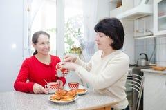 Femmes à la table de cuisine avec la tasse de thé Photo stock