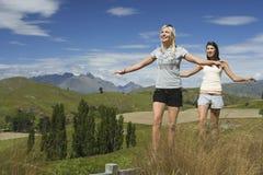 Femmes équilibrant sur la barrière Against Mountains Photographie stock libre de droits
