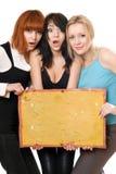 Femmes étonnés prenant un panneau Image stock