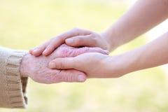 Femmes aînés et jeunes retenant des mains Images stock