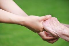 Femmes aînés et jeunes retenant des mains Photographie stock