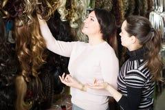 Femmes achetant agrafe-dans l'extension naturelle de cheveux Photos stock