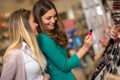 Femmes achetant et regardant des cosmétiques Image stock
