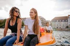 Femmes adolescentes s'asseyant sur le bateau de pédale Image libre de droits