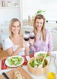 Femmes adorables faisant tinter des glaces de vin rouge Image libre de droits