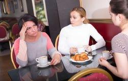 Femmes adultes tristes buvant du café dans le cafétéria Photos stock