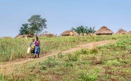 Femmes africaines allant obtenir l'eau dans le village en Ouganda, Afric Photographie stock libre de droits