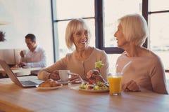 Femmes agées agréables causant tout en mangeant en café Photos stock