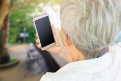 Femmes agées asiatiques s'asseyant en parc tenant le smartphone Image stock