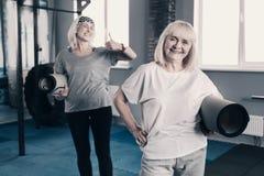 Femmes agées gaies posant avec des tapis de yoga Photographie stock