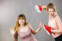 Femmes agressives combattant utilisant des chaussures avec la femelle Photographie stock