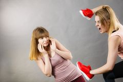 Femmes agressives combattant utilisant des chaussures avec la femelle Image stock
