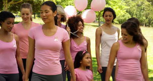 Femmes allant sur une promenade pour la conscience de cancer du sein en parc banque de vidéos