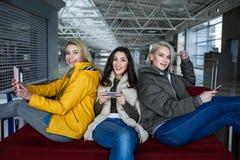Femmes appréciées sur le sofa utilisant des smartphones avant l'embarquement Image stock