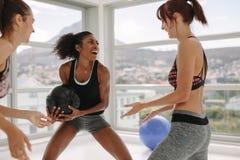 Femmes appréciant l'exercice avec le medicine-ball au gymnase Photos libres de droits