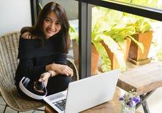 Femmes asiatiques à l'aide de l'ordinateur portable au café urbain image libre de droits