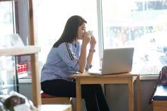 Femmes asiatiques attirantes appréciant son café de matin seul au magasin de gâteau avec l'ordinateur portable images stock