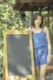 Femmes asiatiques avec la peau brune de cheveux courts et conseil en bois pour la conception image libre de droits